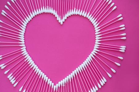 bastoncini di cotone disposti a forma di cuore su uno sfondo rosa. Archivio Fotografico