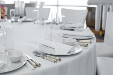 served table in the restaurant. clean white dishes layout on a white tablecloth.