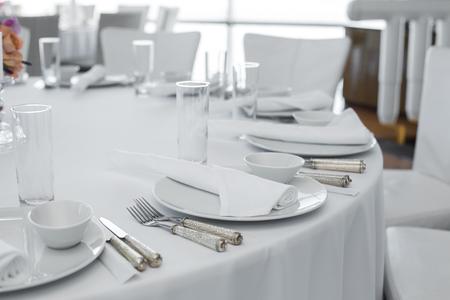 table servie au restaurant. Disposition de vaisselle blanche propre sur une nappe blanche.