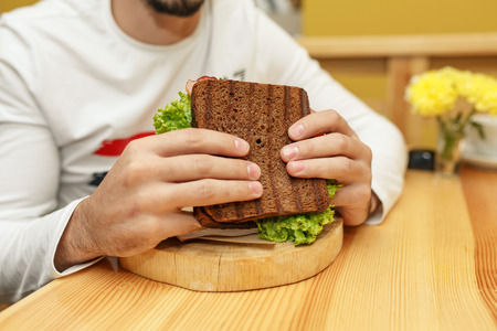 Hungry young man in resaurant eat sandwich.
