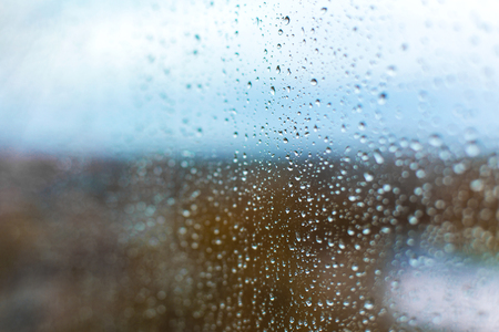 raindrops on the glass against the backdrop of the autumn city.