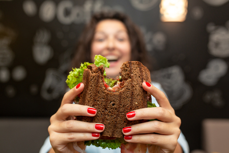 Closeup lustiges verschwommenes Protrait der jungen Frau halten gebissenes Sandwich von ihren beiden Händen. Sandwich im Fokus. dunkler Hintergrund.