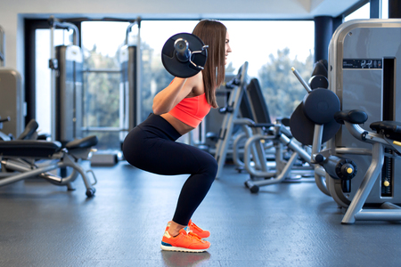 slim handsome young woman in sportswear squats with a barbell on the shoulder in the gym.
