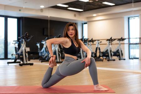 Jeune femme faisant des exercices d'étirement dans la salle de gym.