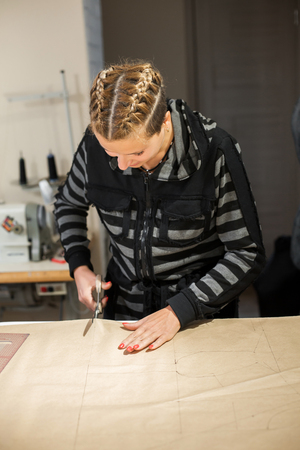 Blonde woman seamstress cuts from craft paper pattern for making clothes.