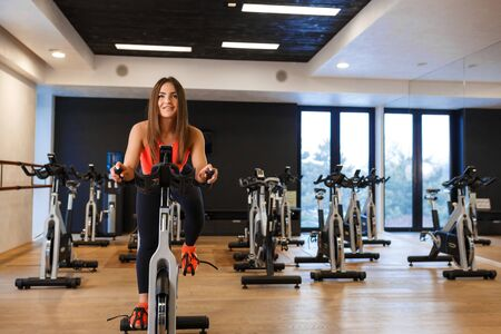 Portrait of young slim woman in sportwear workout on exercise bike in gym. Sport and wellness lifestyle concept.