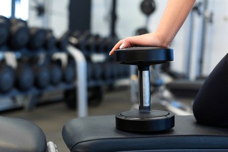 Closeup woman hands with dumbbells on bench in gym.