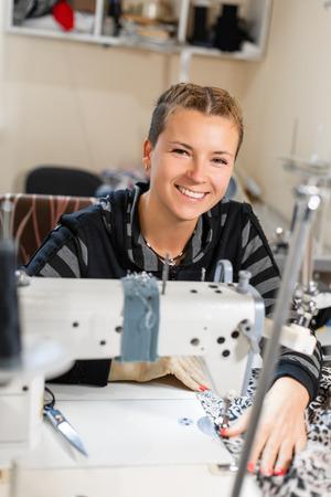 Näherin näht an der Maschine, Porträt. Nähmaterial des weiblichen Schneiders am Arbeitsplatz. Vorbereiten von Stoffen für die Kleiderherstellung. Schneiderei, Bekleidungsindustrie, Designerwerkstattkonzept. Standard-Bild