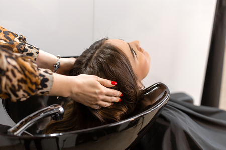 Haircut master washes hair of her clients had. 写真素材