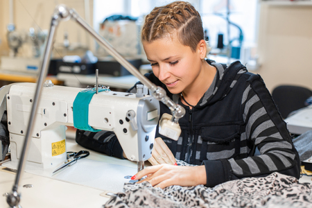 Seamstress sewing at machine, portrait. Female tailor stitching material at workplace. Preparing fabric for clothes making. Tailoring, garment industry, designer workshop concept.