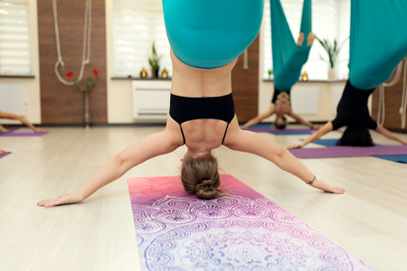 woman hang upside down in a hammock. fly yoga class in the gym. Fit and wellness lifestyle. Stockfoto