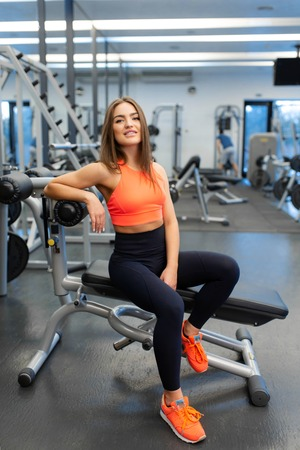 Portrait of slim handsome young woman relax in gym after hard training.