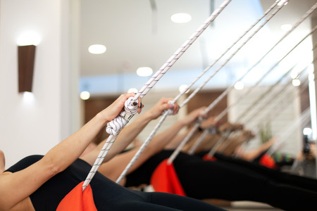 woman practicing yoga on ropes stretching in gym. Fit and wellness lifestyle. Reklamní fotografie - 122692011
