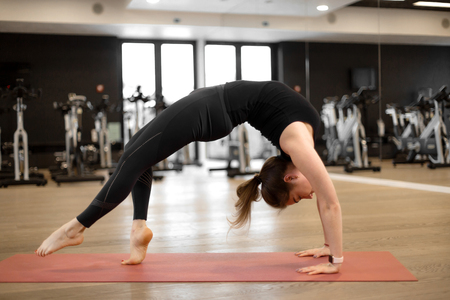 The girl in the gym does yoga to keep herself in shape or control excess weight Stock Photo