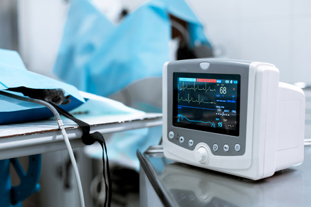 Cardiac monitor at operating table with dog on background. Pet surgery. Reklamní fotografie