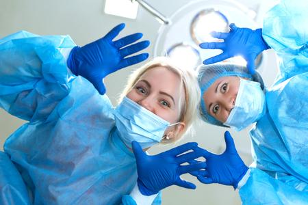 junge Frauenchirurgen lustiger Scherz vor der Kamera im Operationssaalhintergrund.