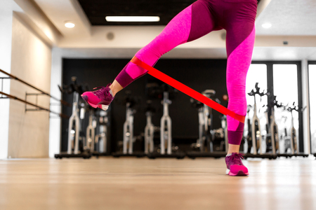 Young woman in sportwear sport exercise with fit rubber band on legs in gym. Fitness and wellness lifestyle concept. Stock Photo