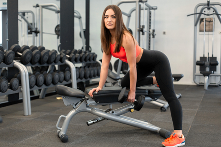 slim woman exercis with dumbbells on bench at gym. Imagens - 124868579