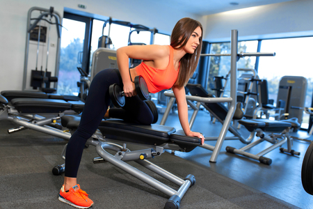 Portrait handsome fit woman lifting dumbbells on bench at gym.