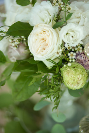 Wedding table setting is decorated with fresh flowers and white candles. Wedding floristry. Bouquet with roses, hydrangea and eustoma.