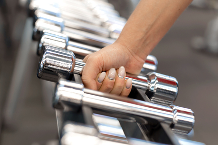 woman hand takes dumbbell form rows of dumbbells in the gym. Imagens