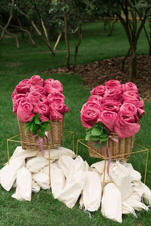 Warm pink blankets rolled up in the form of roses in a large basket for guests at an outdoor wedding party. Individual dance white slippers for guests at the wedding. Dance shoes in bags. 免版税图像