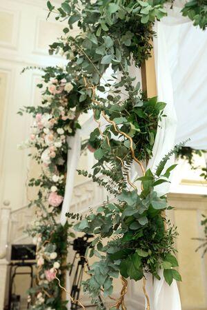 Wedding chuppah decorated with fresh flowers indoor banquet hall of wedding ceremony. Luxury wedding florist decoration artwork.