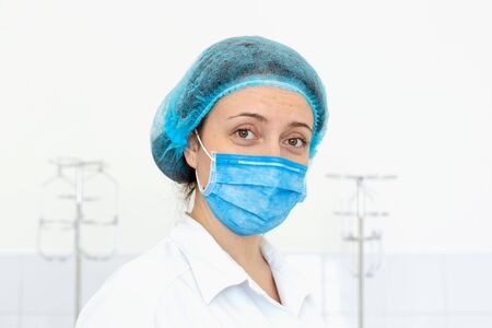 Portrait of a young nurse in medical outfit and face mask. 免版税图像