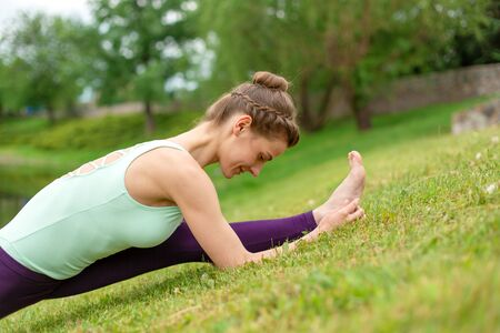 Slender young brunette yogi performs complex yoga exercise on green grass in the summer on a background of nature.