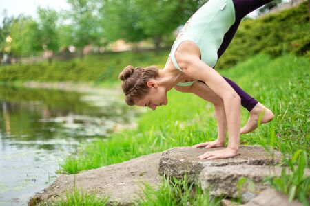 Slim brunette girl doing yoga in the summer on a green lawn by the lake.