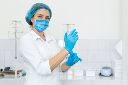 Nurse in scrub and mask puts gloves on her hands.