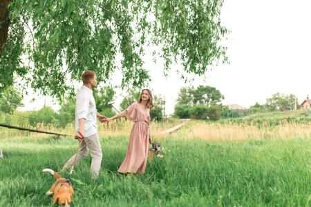 Young loving couple having fun and running on the green grass on the lawn with their beloved domestic dog breed Beagle and a bouquet of wildflowers. Stock Photo