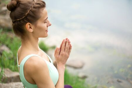 Thin brunette girl plays sports and performs beautiful and sophisticated yoga poses in a summer park. Green forest and the river on the background. Woman doing exercises on the yoga mat. Lotus pose.