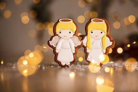 Holiday traditional food bakery. Gingerbread pair of little cute angels boy and girl in cozy warm decoration with garland lights. Imagens