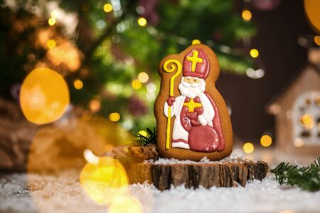 Holiday traditional food bakery. Gingerbread catholic preacher in cozy decoration with garland lights and cup of hot coffee. Stock Photo