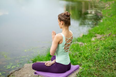 Slender Caucasian brunette girl doing yoga in summer on a green lawn by the river. 写真素材