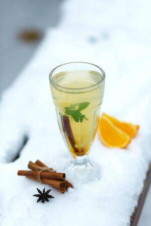 glass of hot vitamin tea on winter snowy bench. winter hot seasonal drinks.