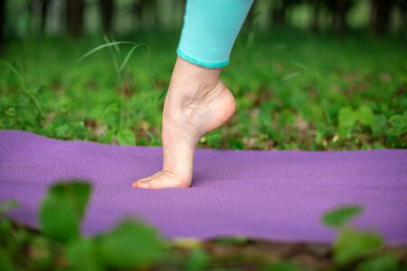 Thin brunette girl plays sports and performs yoga poses in a summer park. Green forest on the background. Woman doing exercises on the yoga mat, feet close-up.