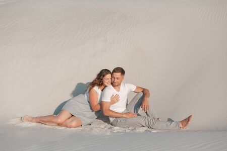 Romantic pair sit on white sand and huggins, in desert.