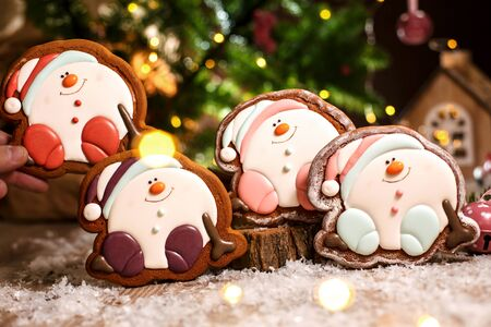 Holiday traditional food bakery. Three Gingerbread happy sitting Snowman or snowball in cozy warm decoration with garland lights.
