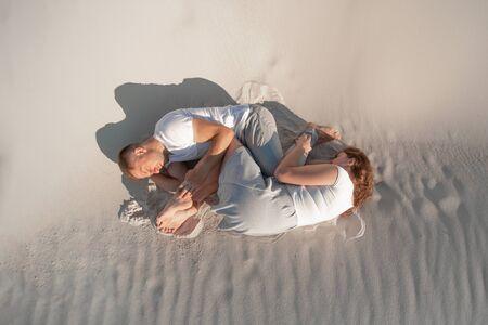 Romantic pair laying on white sand in desert.
