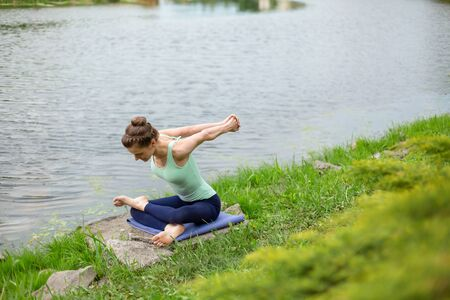 Thin brunette girl plays sports and performs beautiful and sophisticated yoga poses in a summer park. Green lush forest and the river on the background. Woman doing exercises on a yoga mat.