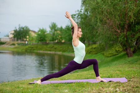 Thin brunette girl plays sports and performs beautiful and sophisticated yoga poses in a summer park. Green lush forest and the river on the background. Woman doing exercises on a yoga mat 写真素材