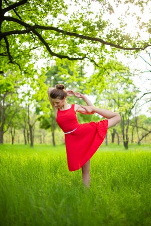 Slim beautiful brunette girl in a red dress performs yoga poses in a summer park. Green forest at sunset.