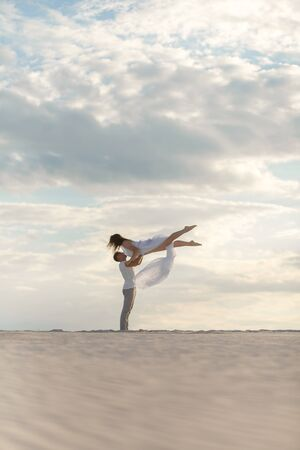 Romantic couple dancing in sand desert. The guy lifts the girl above himself. Sunset sky.