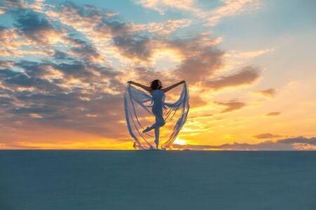 A girl in a fly white dress dances and poses in the sand desert at sunset. Banco de Imagens