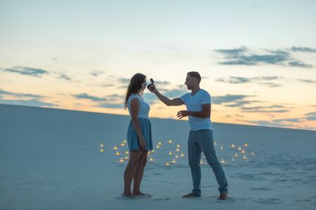 The guy makes the girl a marriage proposal at evening in sand desert.