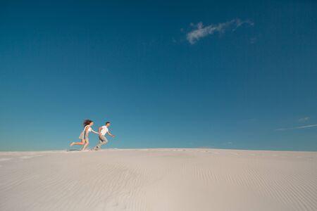 Romantic couple in love running on white sand in desert.