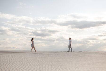Couple meeting in white sand desert at sunset.