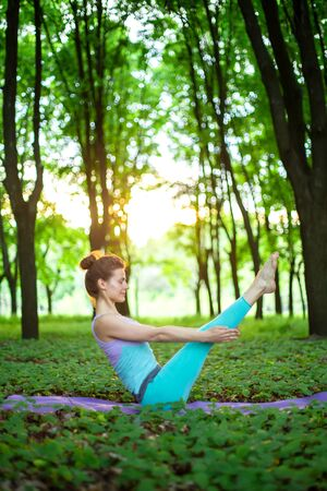 Thin brunette girl plays sports and performs yoga poses in a summer park on a sunset background. Woman doing exercises on the yoga mat. Summer forest. Soft focus.